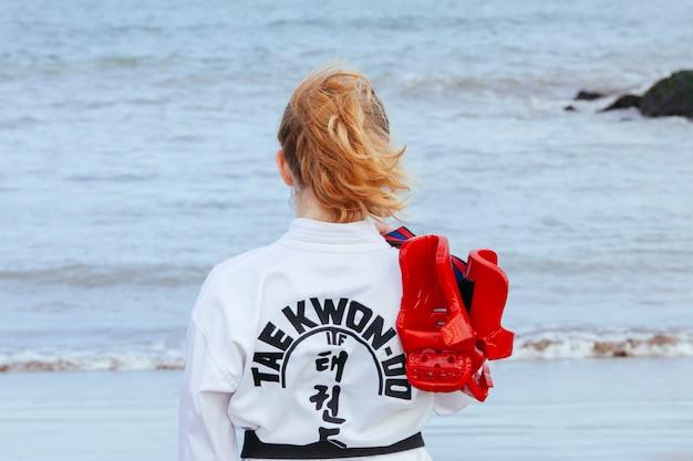 Forte giovane donna con guanti taekwondo che imparano le arti marziali