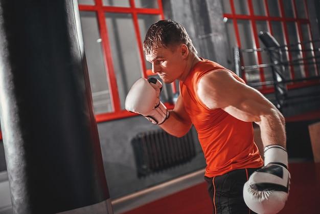 Sportivo bello più forte e più veloce nell'allenamento di abbigliamento sportivo su sacco da boxe pesante nel pugilato