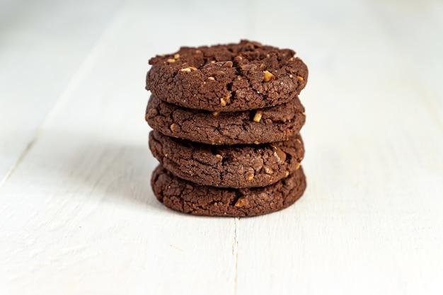 Bloccato di biscotti al cioccolato americani fatti in casa con noci su fondo di legno bianco. pasticceria fresca.