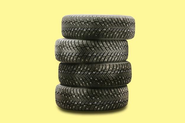 Pneumatici chiodati, un set di 4 pezzi su uno sfondo giallo per il cambio stagionale dei pneumatici.