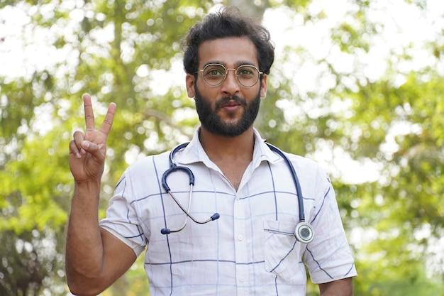 Uno studente ha ottenuto una borsa di studio in un corso di educazione medica o collage - studente con lo stetoscopio e mostrando il segno di successo della vittoria - concetto di educazione medica