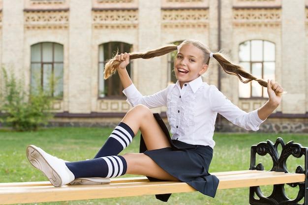 Adorabile bambino studente in uniforme formale che si rilassa all'aperto. piacevoli minuti di riposo. tempo per rilassarsi e divertirsi. rilassarsi nel cortile della scuola. studentessa perfetta che si rilassa tra le lezioni. equilibrio di vita.