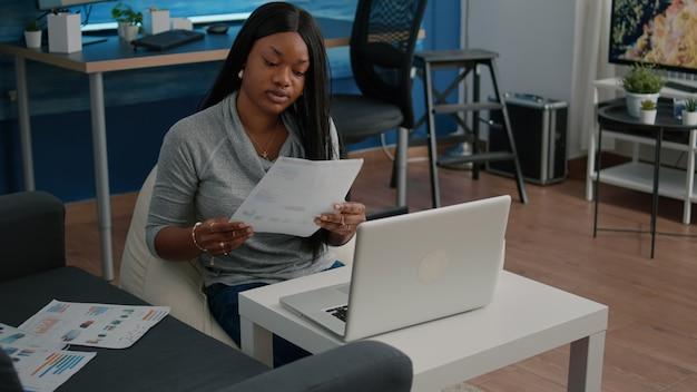 Studente che analizza il grafico dei documenti finanziari digitando la presentazione delle infografiche che lavora a distanza da casa inviando e-mail alla società