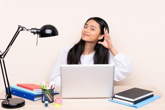 Ragazza asiatica dell'allievo in un posto di lavoro con un computer portatile isolato sul beige ascoltando qualcosa mettendo la mano sull'orecchio