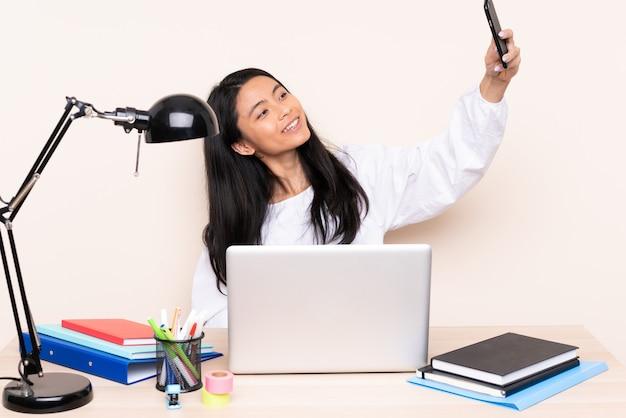 Ragazza asiatica dell'allievo in un posto di lavoro con un computer portatile isolato sul beige che fa un selfie