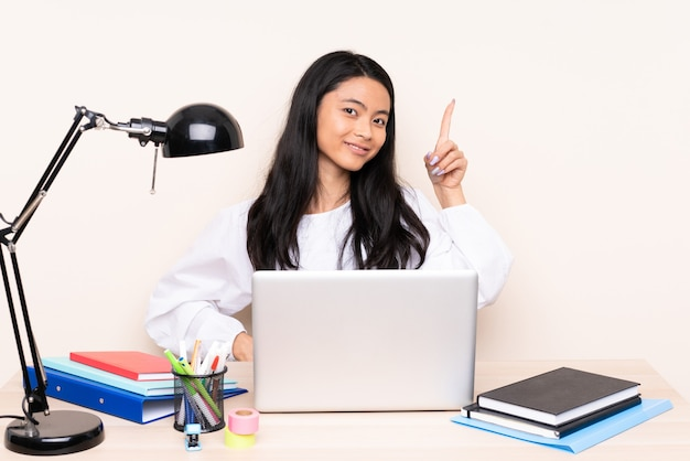Ragazza asiatica dell'allievo in un posto di lavoro con un computer portatile isolato sulla rappresentazione beige e alzando un dito in segno del meglio
