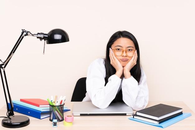 Ragazza asiatica dell'allievo in un posto di lavoro con un computer portatile isolato sulla parete beige