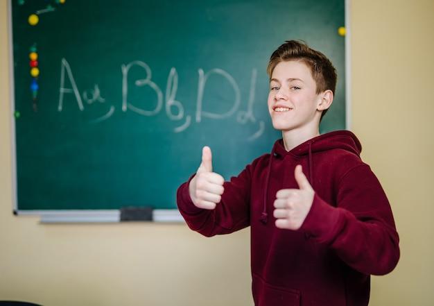 Ragazzo studente in piedi davanti alla lavagna in classe a scuola. concetto di educazione.