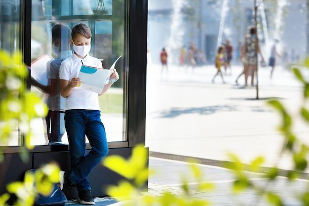 Studente ragazzo che indossa la maschera sta leggendo un libro in piazza della città durante la pandemia covid 19