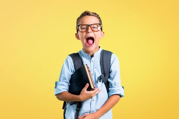 Ragazzo dell'allievo con lo zaino e vetri che ridono su fondo giallo. di nuovo a scuola