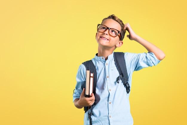Studente ragazzo con zaino e occhiali in piedi e pensando un'idea. di nuovo a scuola