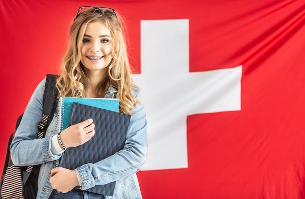 Studente in bretelle sorride tenendo il materiale di studio dalla bandiera della svizzera.