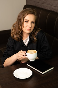 Studente in caffè che beve caffè leggendo il libro bestseller