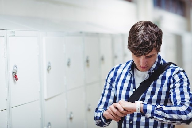 Studente che controlla tempo sull'orologio nello spogliatoio