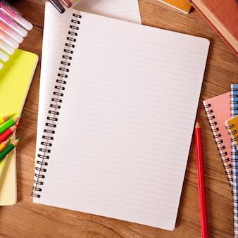 Scrittorio dello studente con il libro di scrittura in bianco, spazio della copia