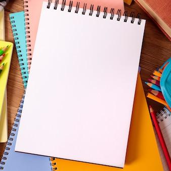 Scrittorio dello studente con il libro di scrittura in bianco