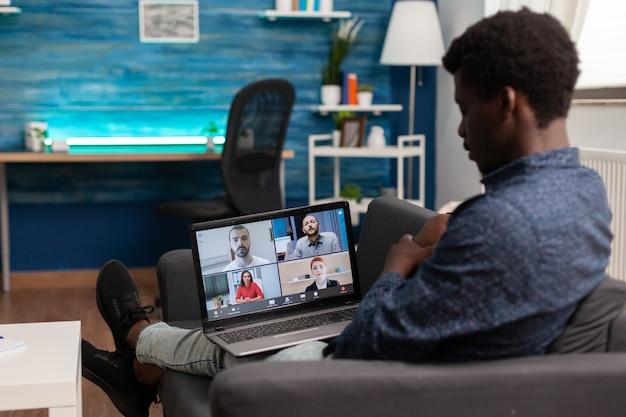 Studente che discute l'idea di business con il team universitario durante la riunione di teleconferenza in videochiamata online utilizzando la piattaforma scolastica di e-learning. telelavoro in conferenza su laptop in soggiorno. utente di computer
