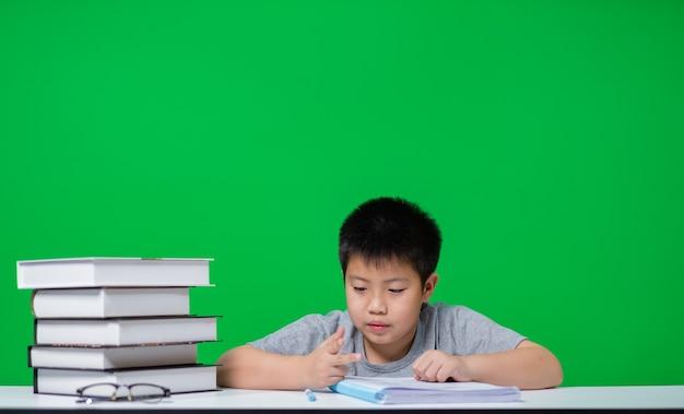 Studente che fa i compiti sullo schermo verde, carta da lettere del bambino, concetto di educazione, torna a scuola