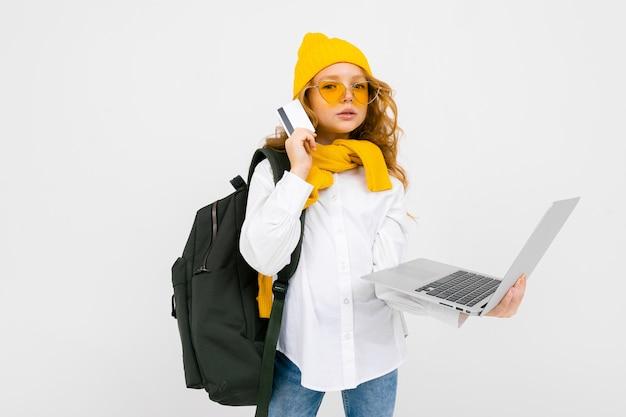 Ragazza dello studente in abbigliamento casual con uno zaino sulle sue spalle e con un computer portatile in sue mani che cammina e che legge le notizie sul bianco