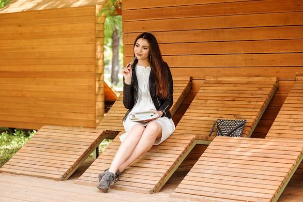 La studentessa è seduta sulla panchina nel campus studentesco e prende appunti nei suoi libri di testo.
