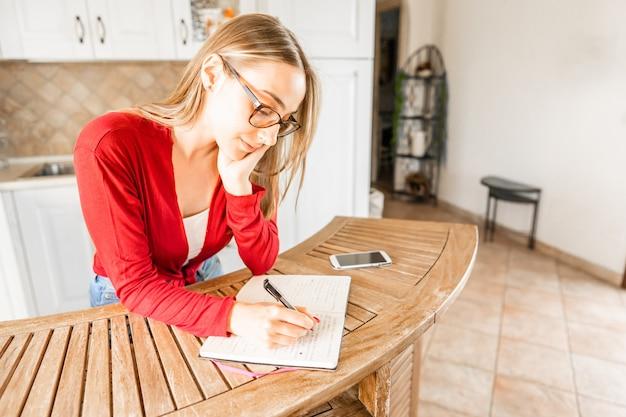 Studentessa che vive da sola tiene le bollette della casa in cucina prendendo appunti su un blocco note. la giovane donna compila una lista di cose da fare durante il giorno scrivendo con la penna in un taccuino. vivere da soli affrontando i costi