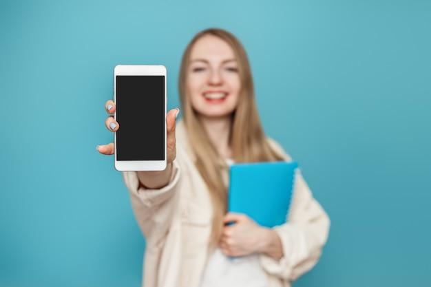 Studentessa mostra uno schermo vuoto di un telefono cellulare alla fotocamera e sorride