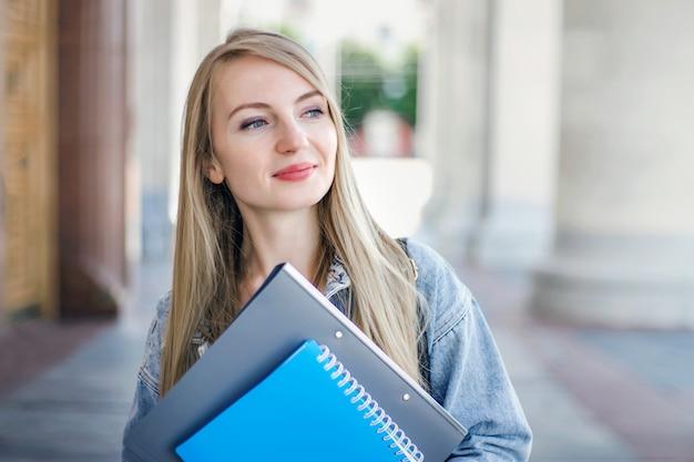 Studentessa si trova sullo sfondo di una vecchia università