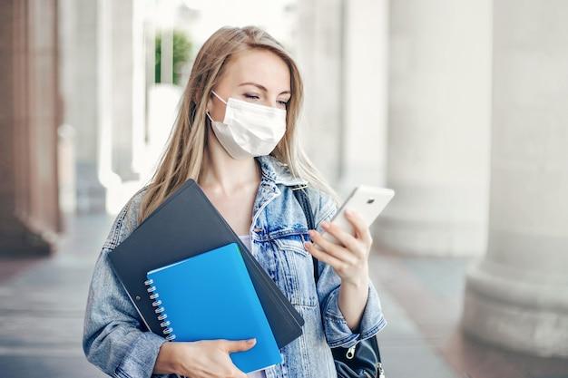 Studentessa che indossa una maschera antivirale protettiva legge i messaggi su un telefono cellulare durante la quarantena della pandemia di coronavirus