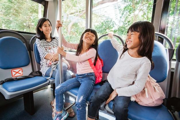 Studenti che vanno a scuola in autobus con i mezzi pubblici insieme