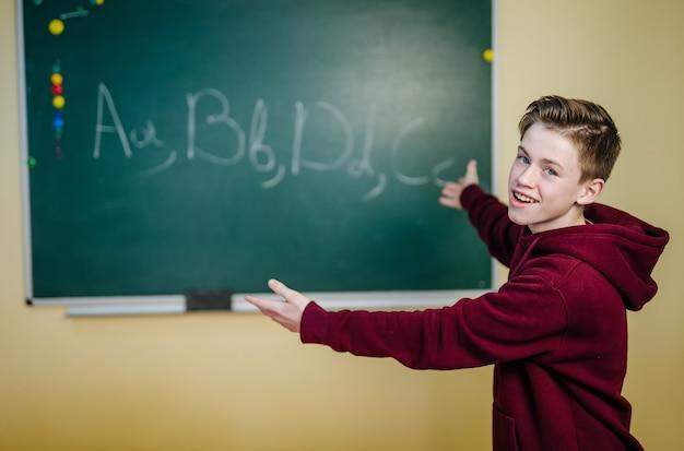 Lo studente della scuola superiore è in piedi con una felpa con cappuccio scura vicino alla lavagna verde in classe. l'adolescente sta scrivendo l'alfabeto sulla lavagna. concetto di educazione scolastica