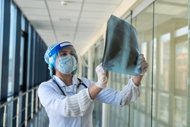 Studente stagista in tuta protettiva e schermo facciale guarda una pellicola a raggi x dei polmoni, covid19. pandemia