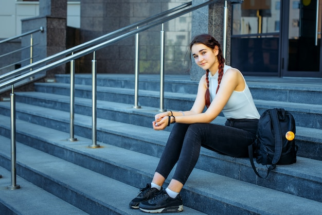 Vita studentesca, esami, sessioni. studentessa con uno zaino seduto sui gradini dell'istituzione