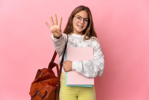 Bambina dell'allievo sopra fondo rosa isolato felice e che conta quattro con le dita