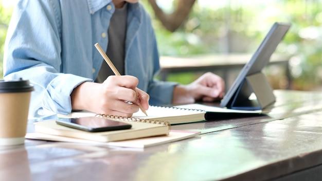 Scrittura a mano dell'uomo dello studente sul taccuino durante l'apprendimento online