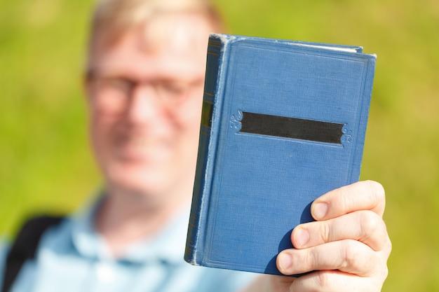 Uomo dello studente che offre un libro