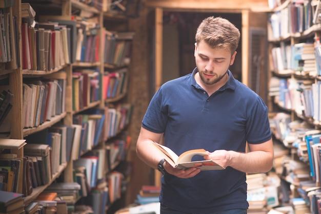 Ritratto dello studente di una barba che sta in una biblioteca pubblica fra gli scaffali e che esamina un libro in sue mani