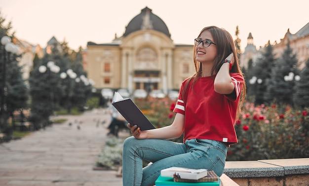 Uno studente con una maglietta rossa è seduto sul gradino con un blocco note aperto e sorride guardando di lato