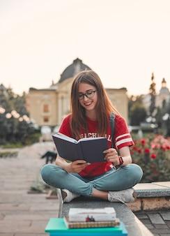 Uno studente con una maglietta rossa con uno zaino è seduto sul gradino, a gambe incrociate e legge un blocco note