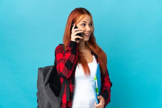 Studente donna russa isolata sul blu mantenendo una conversazione con il telefono cellulare