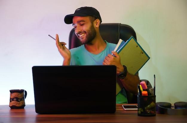 Uno studente sorridente e seduto con un laptop