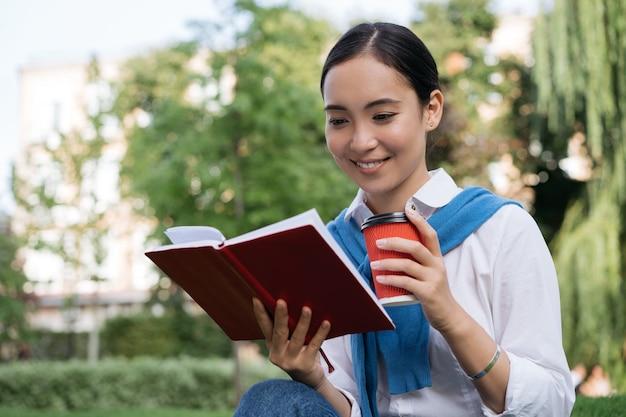 Studente che studia, impara la lingua, seduto nel parco, concetto di educazione