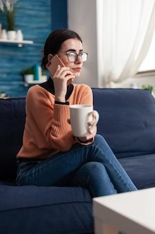 Studente che parla con i suoi amici dei social media utilizzando uno smartphone moderno, rilassandosi da solo sul divano durante la quarantena del coronavirus. adolescente che spettegola mentre beve caffè