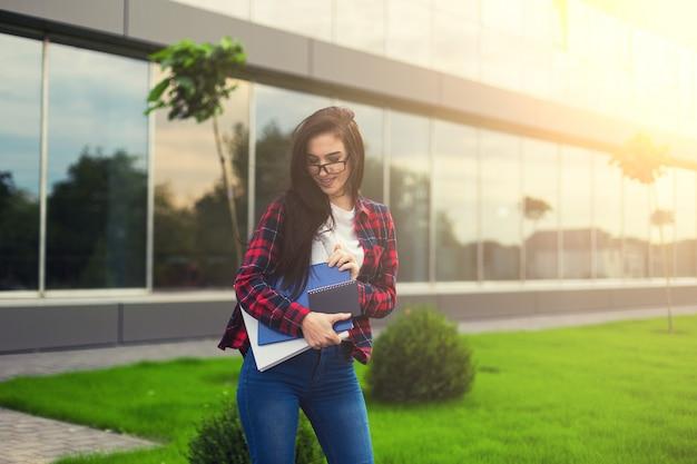 Ragazza teenager dell'allievo in vestito casuale che tiene i libri e che sorride alla macchina fotografica mentre levandosi in piedi