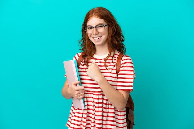 Ragazza rossa dell'adolescente dello studente isolata su fondo blu che celebra una vittoria