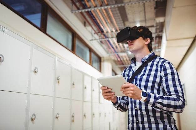 Studente in cuffia avricolare di realtà virtuale facendo uso della compressa digitale nello spogliatoio
