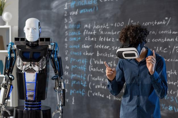 Studente in cuffia vr in piedi dalla lavagna con formula e operante da robot di automazione tramite controllo virtuale