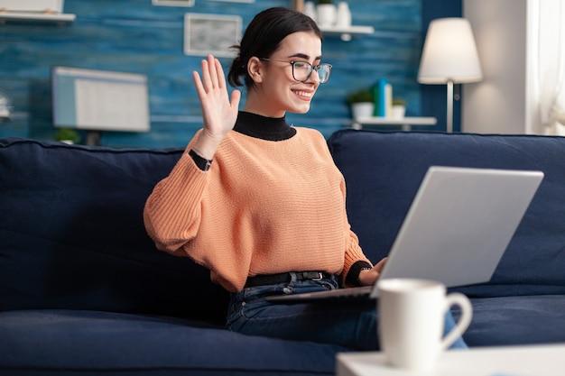 Studente che saluta i suoi amici durante la videochiamata online seduta sul divano nel soggiorno. giovane donna che utilizza webinar virtuale web mobile internet vlass sulla riunione in videoconferenza