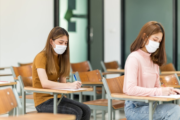 Uno studente che indossa una maschera è seduto in una classe all'università.
