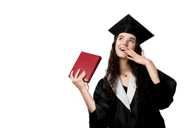 Studente con libro in veste di laurea e berretto pronto per finire il college. accademico giovane donna in abito nero sorridente.