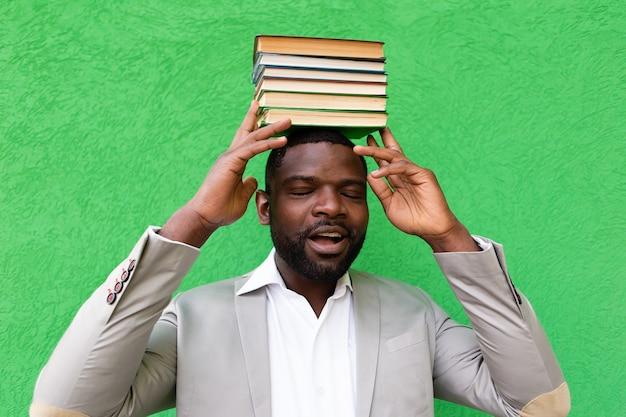 Lo studente con un libro su una parete verde